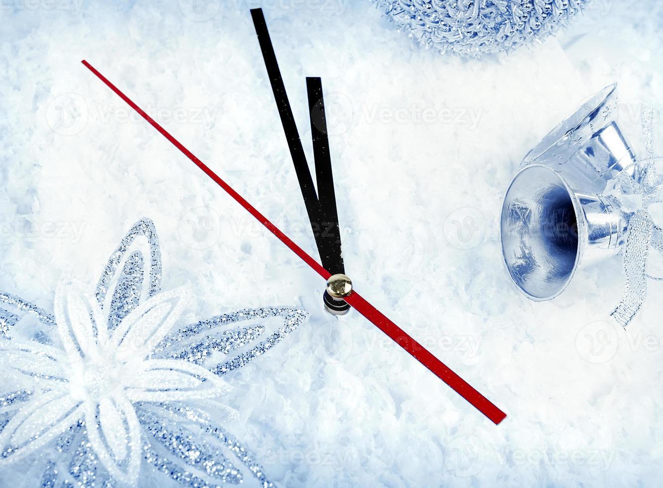 reloj con ramas de abeto y adornos navideños bajo nieve clo foto
