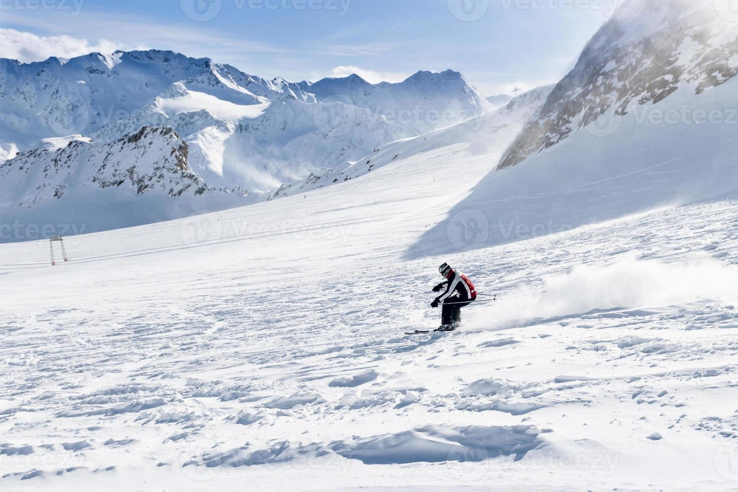 Young skier downhill on the ski slope photo