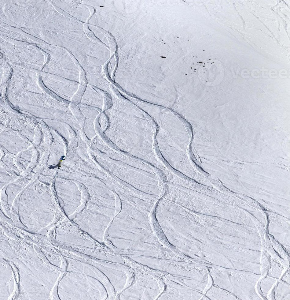 snowboarder cuesta abajo en pendiente fuera de pista con nieve recién caída foto