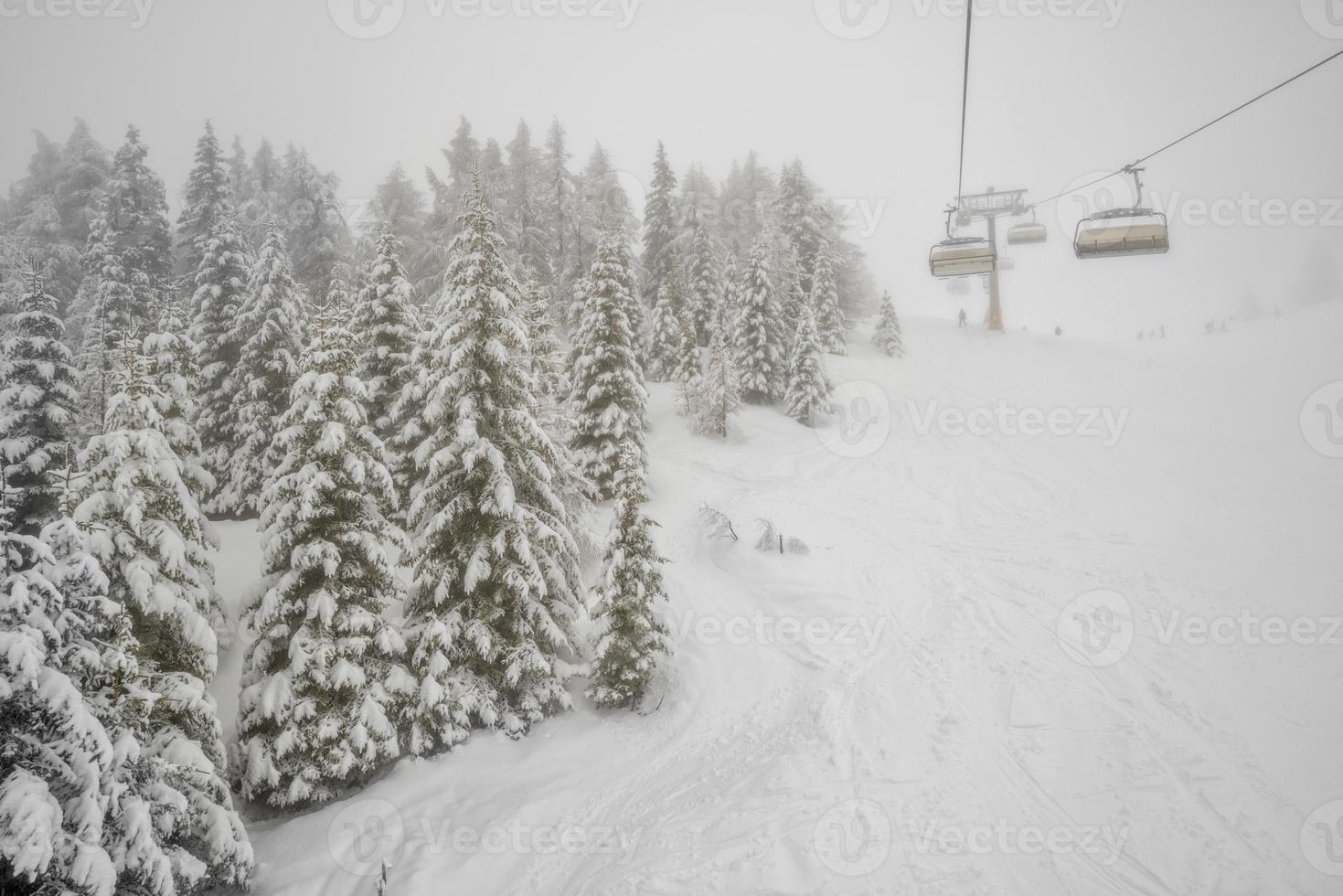 Chairlift in snowfall at alpine ski resort photo