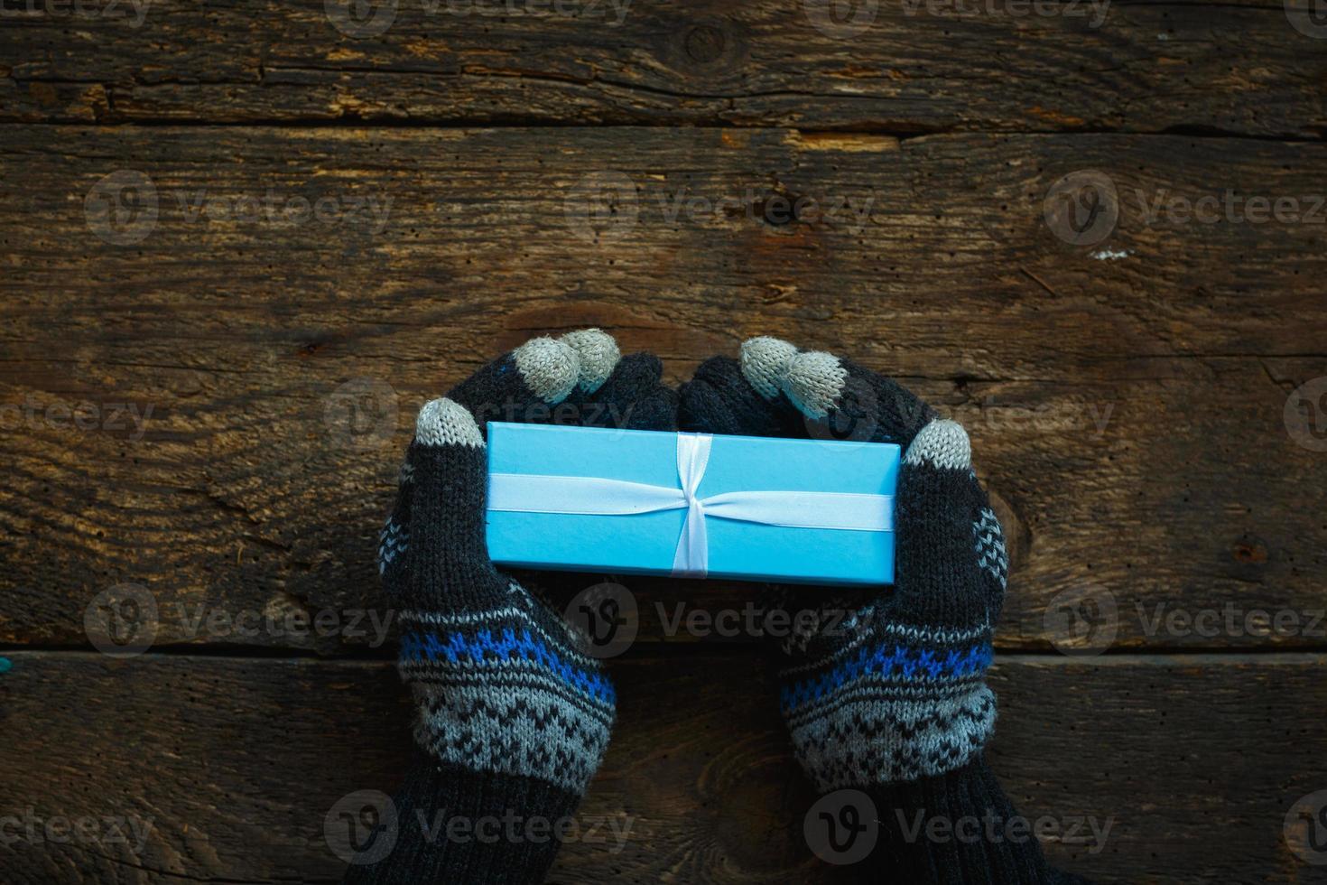 manos en guantes de invierno con caja de regalo de navidad foto