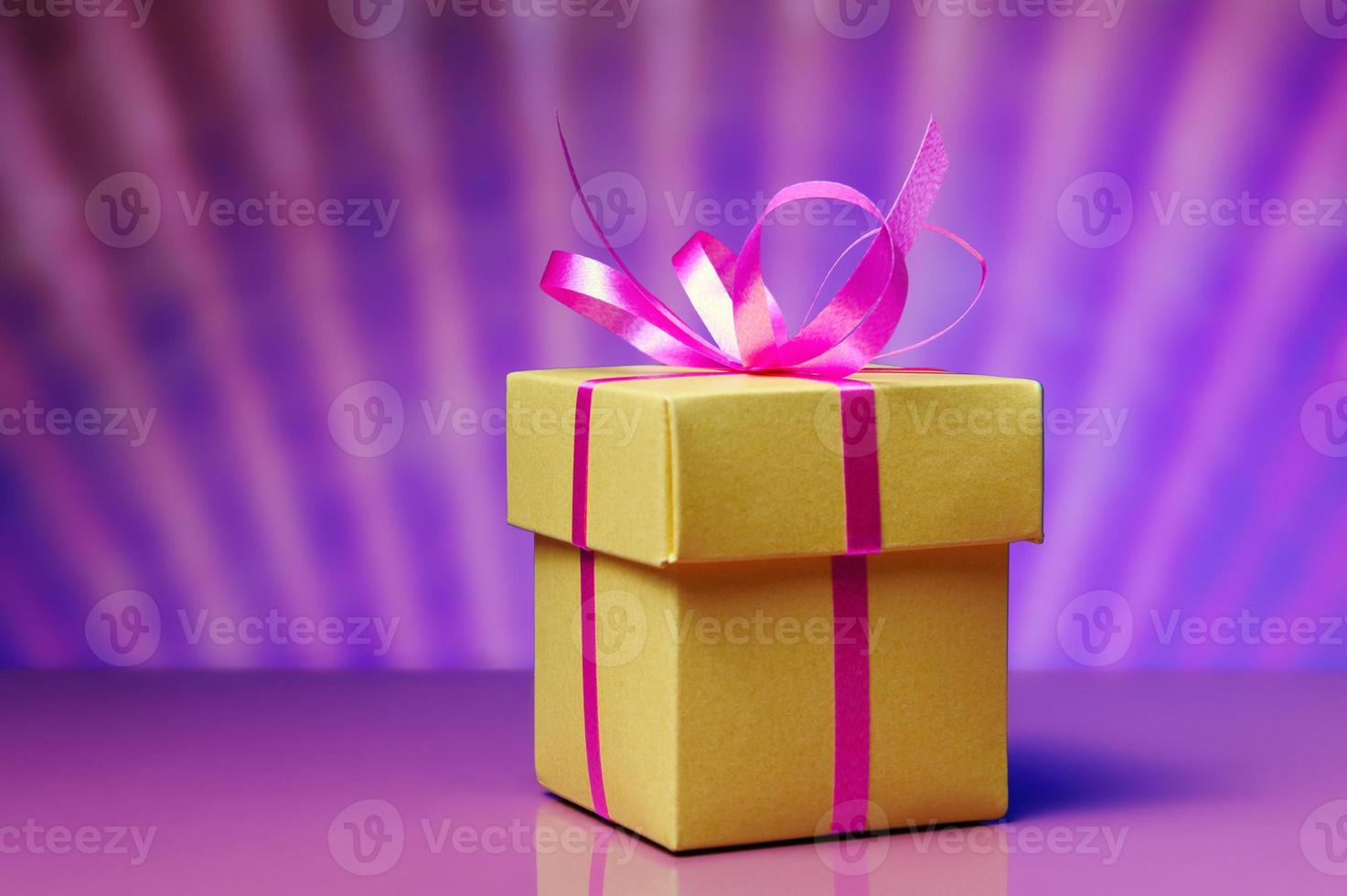 Gift box with pink ribbon on abstract background photo