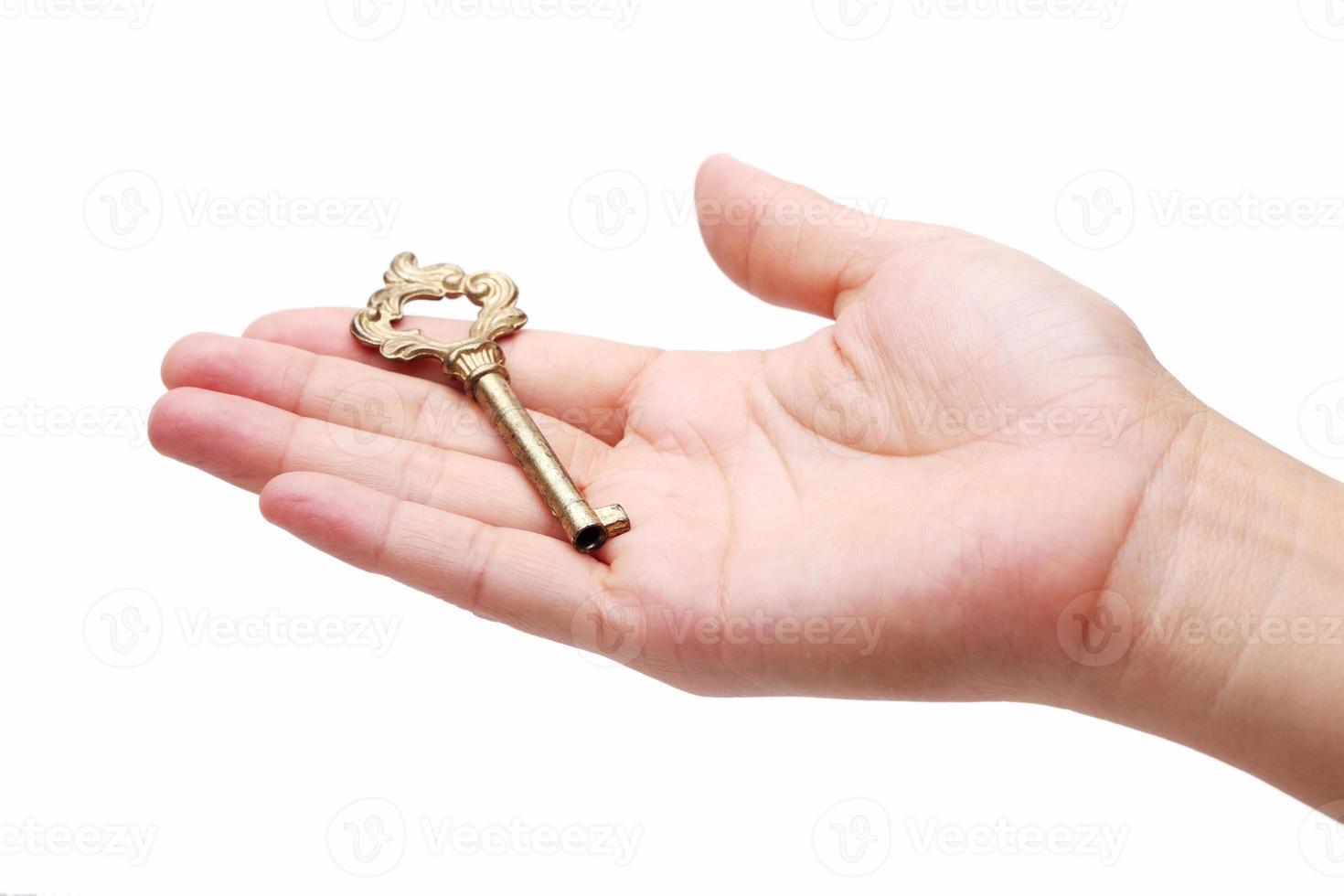Mano sosteniendo la llave de oro aislada sobre fondo blanco. foto
