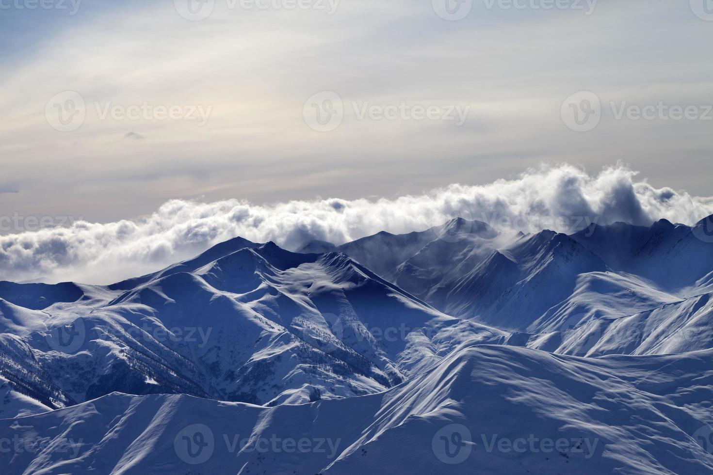Snowy mountains in mist at winter evening photo
