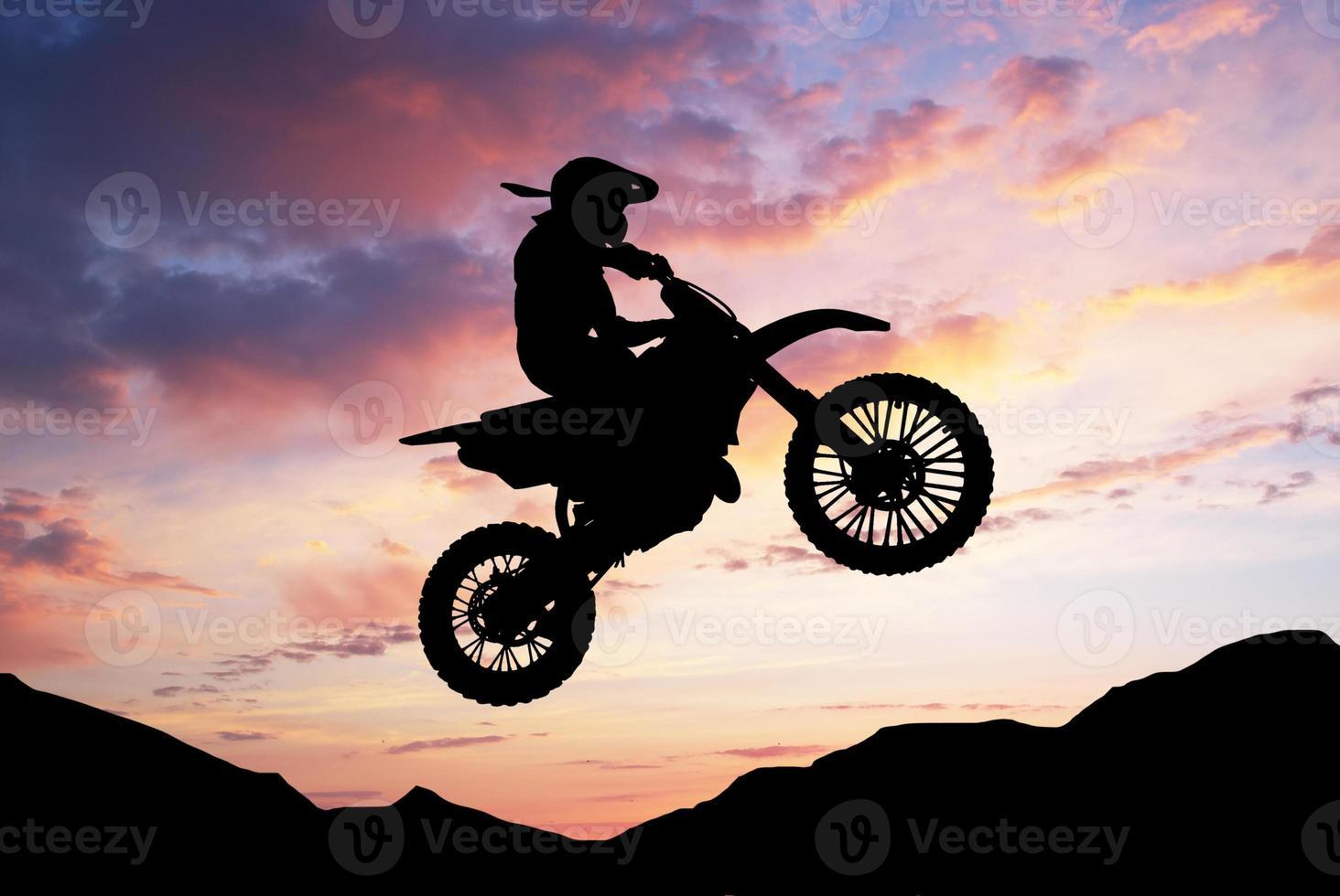 Silhouette of motorbiker photo