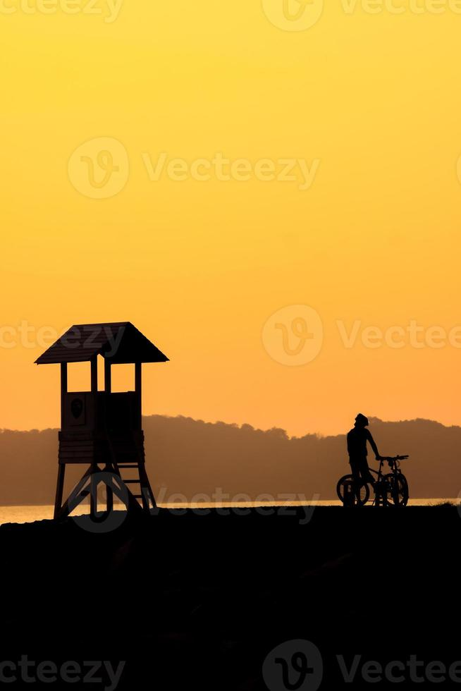 Silhouette of cyclist at sunset. photo
