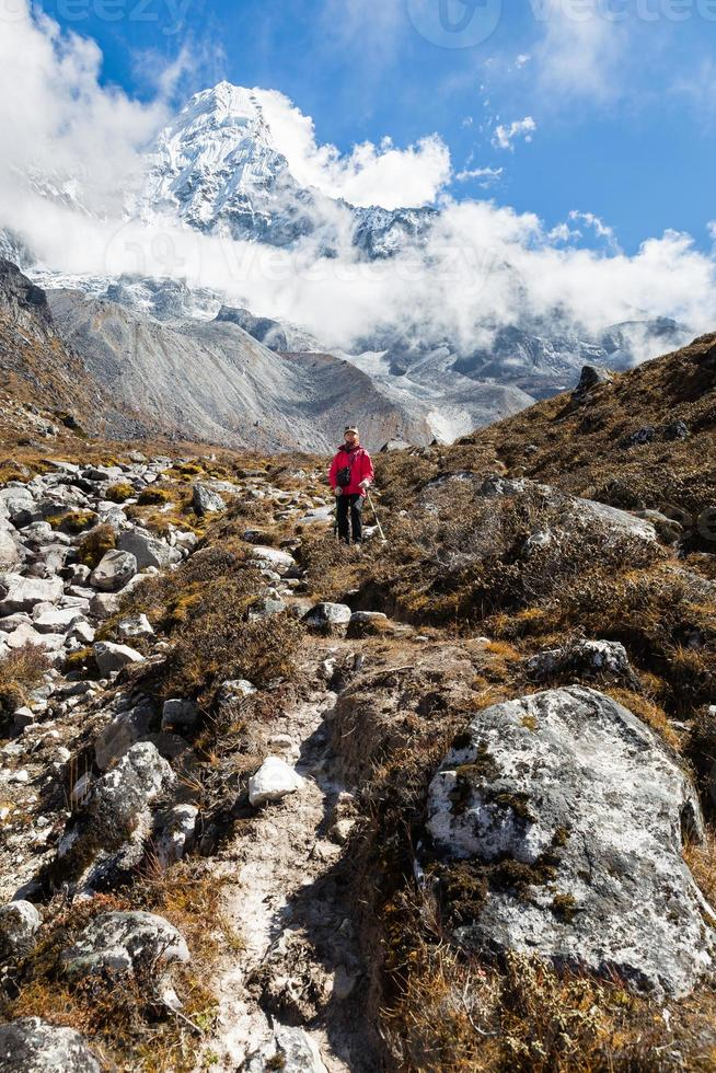 mujer mochilero pie sendero ama dablam montaña. vertical. foto