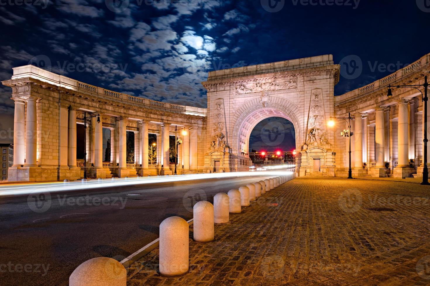 Arco triunfal y columnata de la entrada del puente de Manhattan a la luz de la luna foto