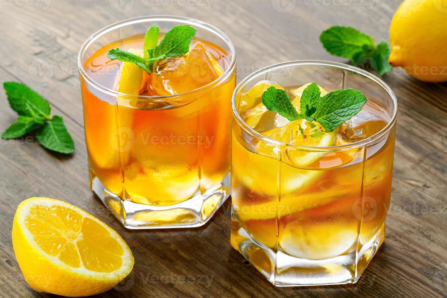 té helado de limón en la mesa de madera marrón con limones alrededor foto