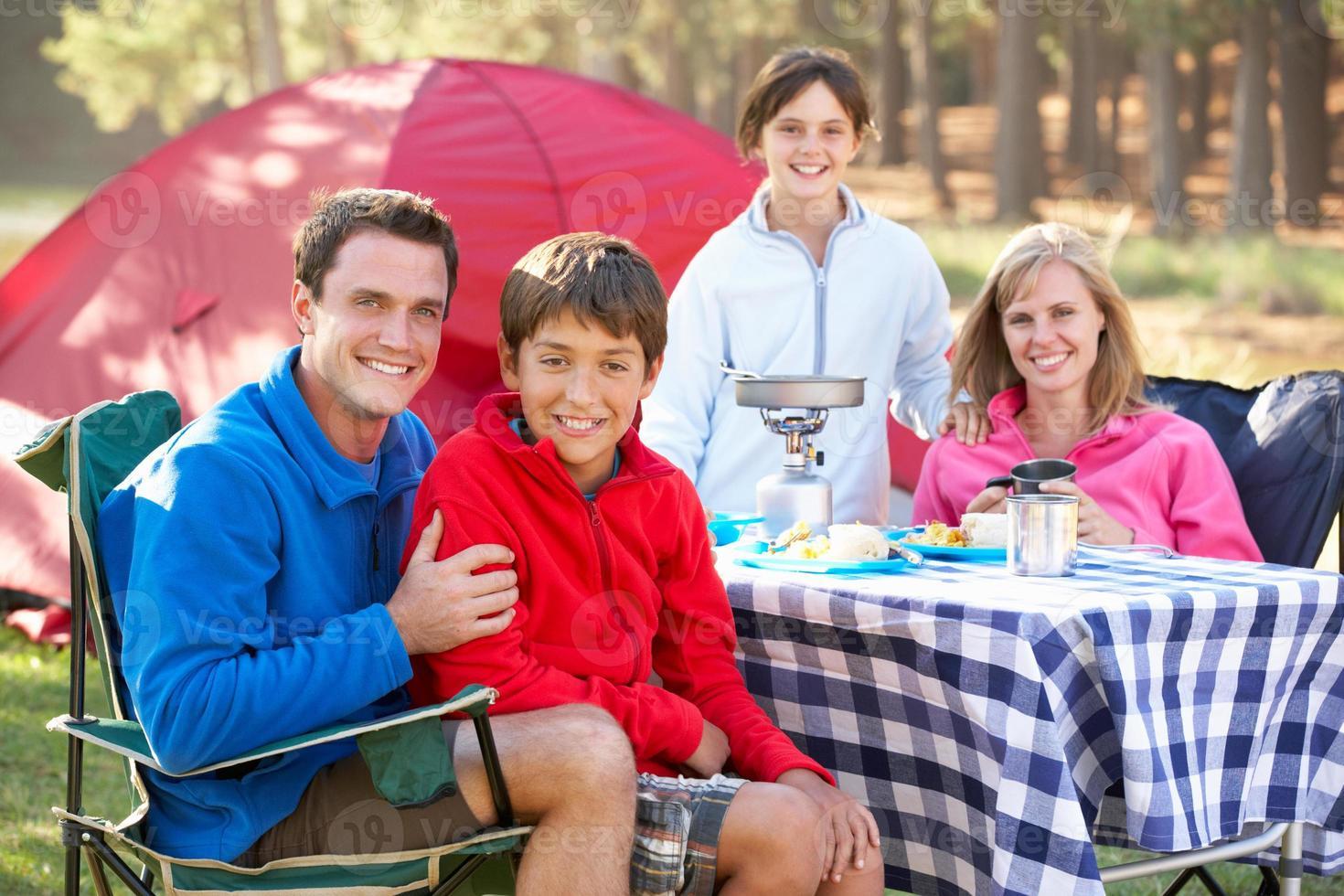 familia disfrutando de comida en vacaciones de camping foto