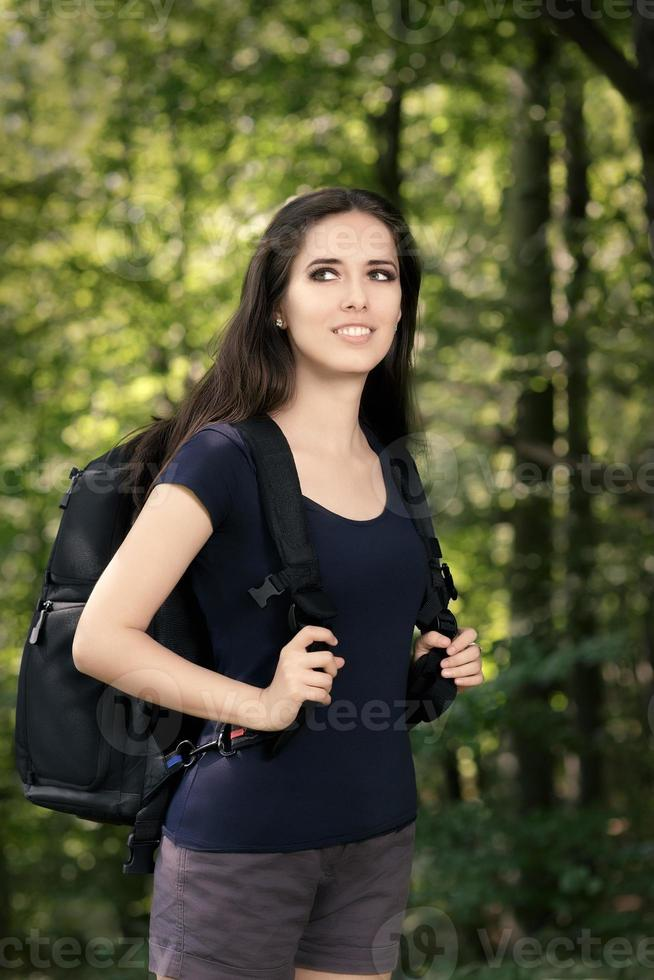 menina feliz caminhadas com mochila de viagem foto