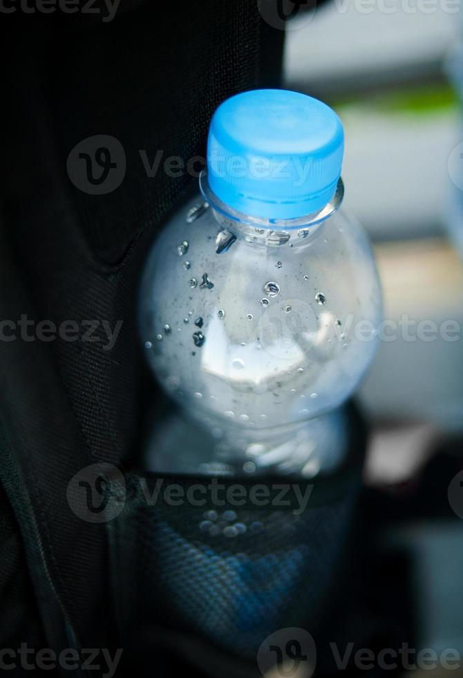 plastic bottle of water in pocket of backpack photo