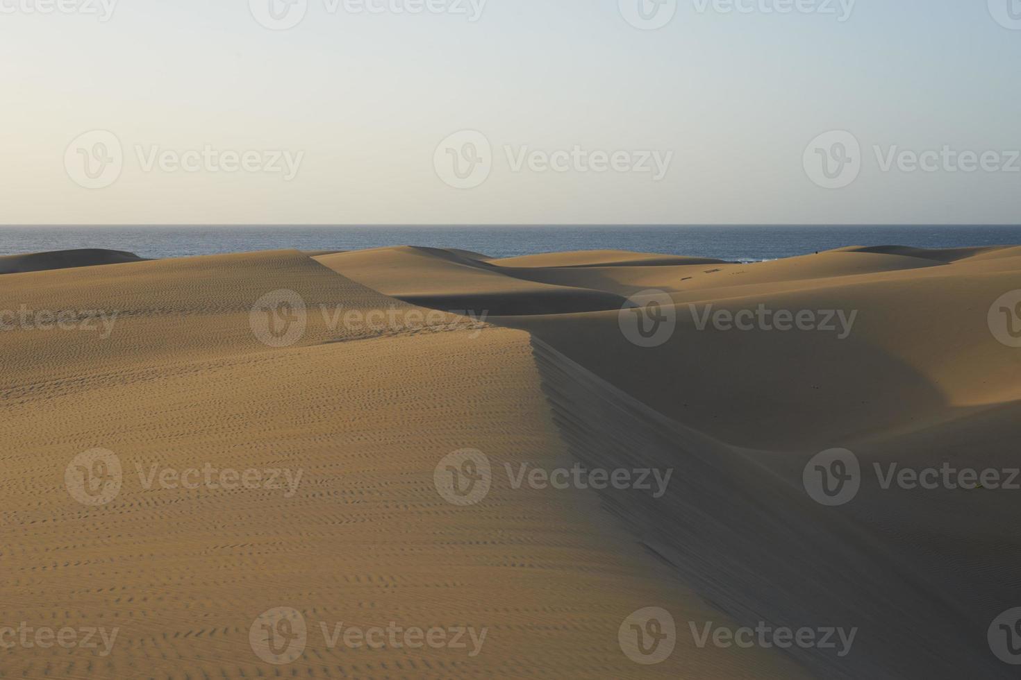 zanderige en golvende duinen in een woestijn van gran canaria foto