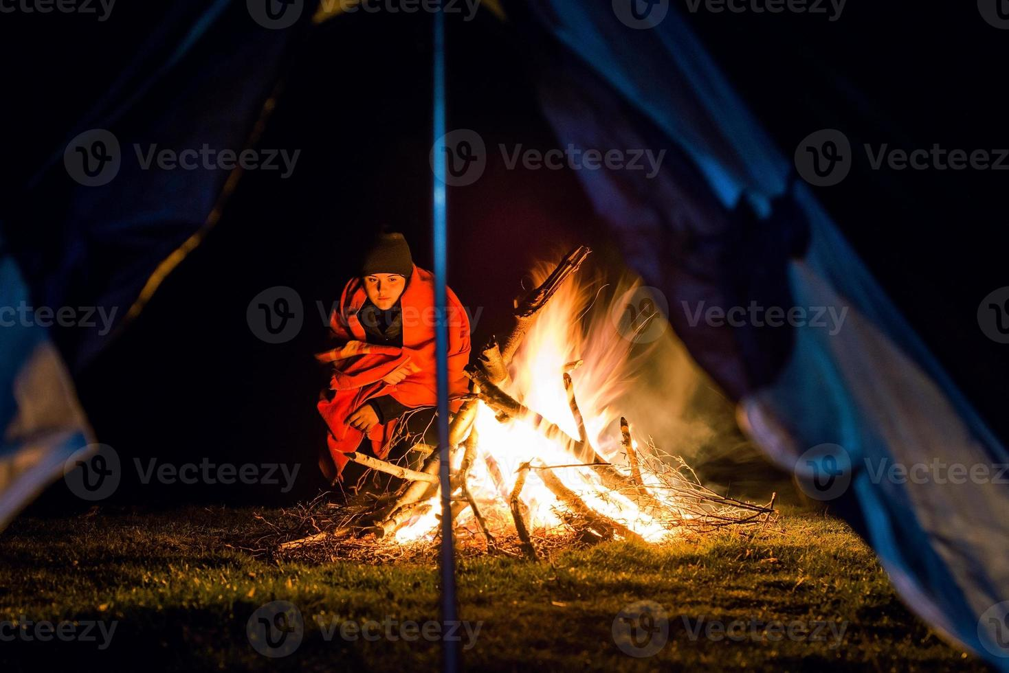 Young girl near camp fire with blanket photo
