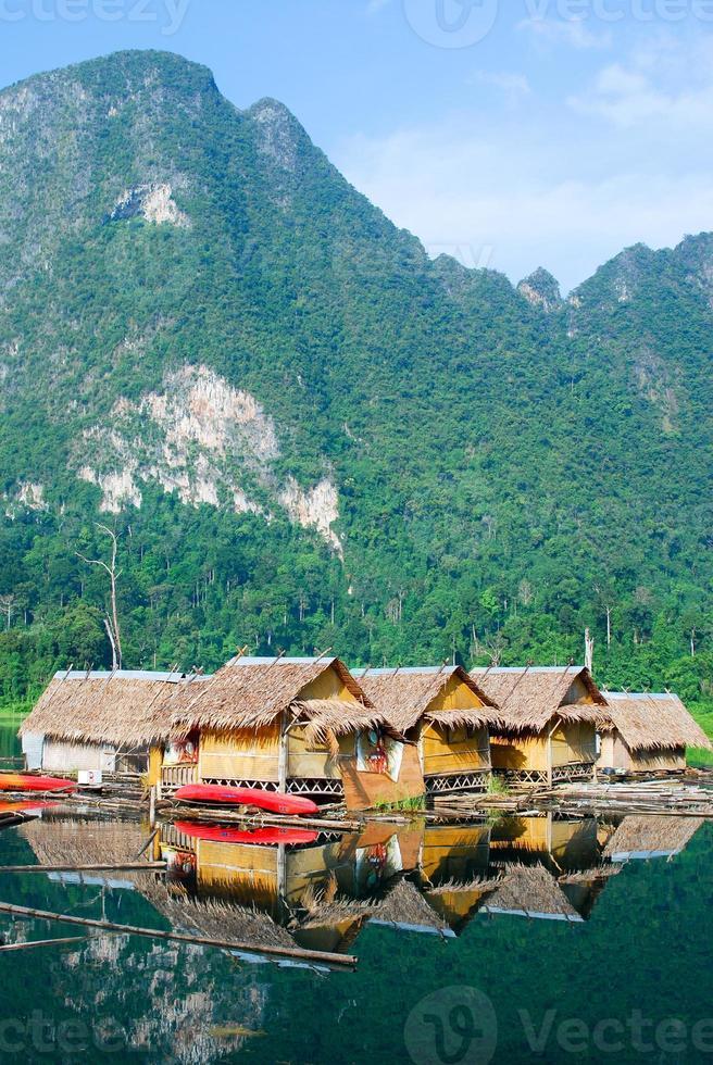 cabana à beira do lago tropical e barco de madeira foto