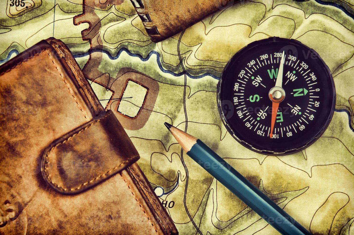 brújula billetera y pasaporte en el mapa antiguo foto