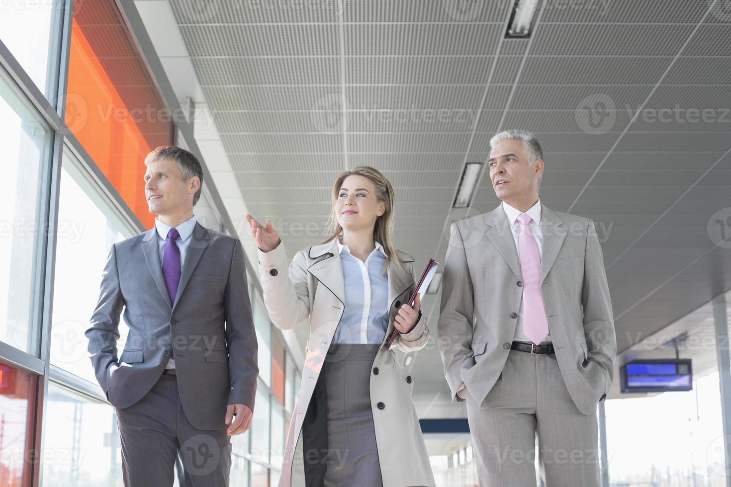 Business people discussing while walking on train platform photo