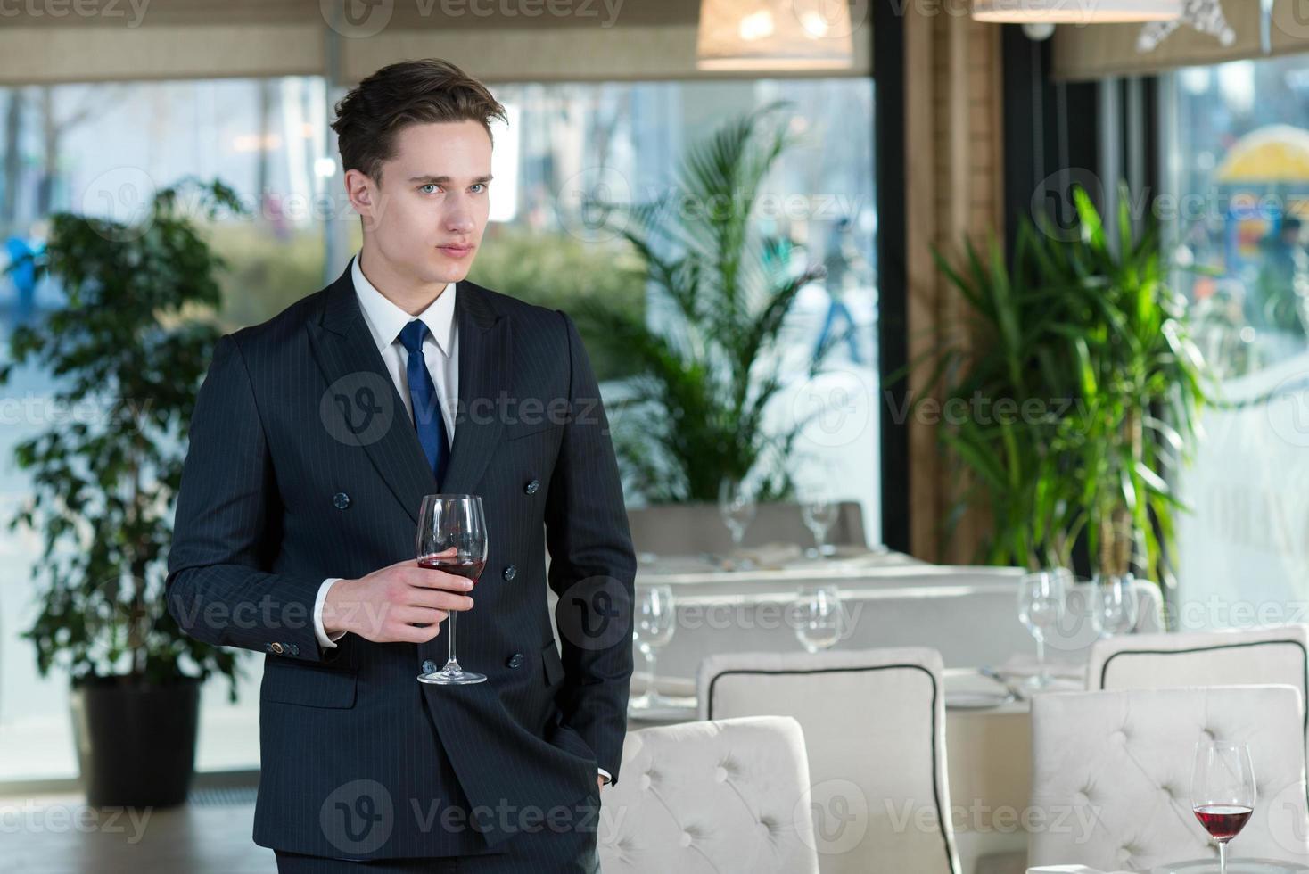 Apuesto hombre de negocios de pie con una copa de vino en el restaurante foto