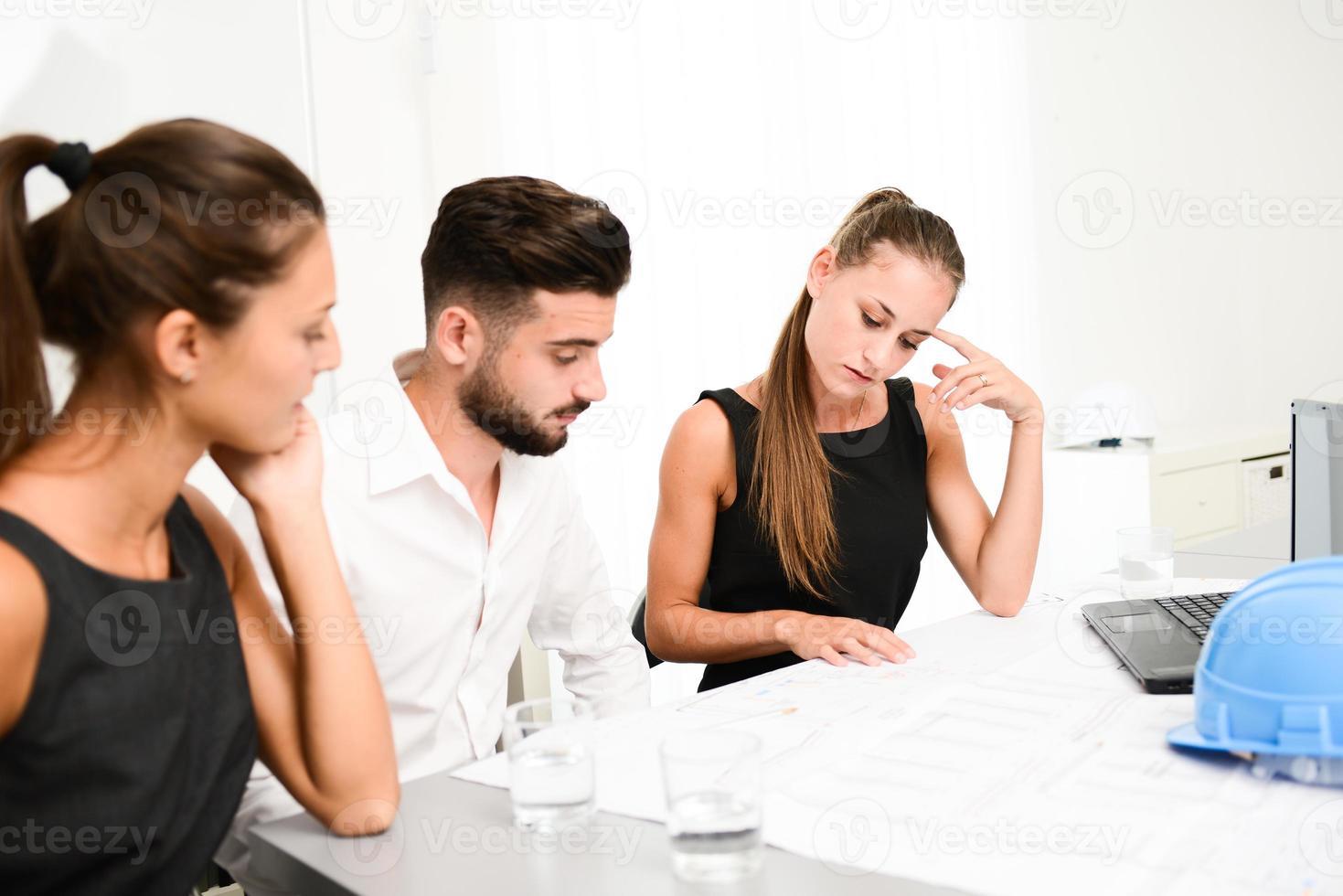 Arquitecto de gente de negocios discutiendo con blueprint en la sala de reuniones de oficina foto