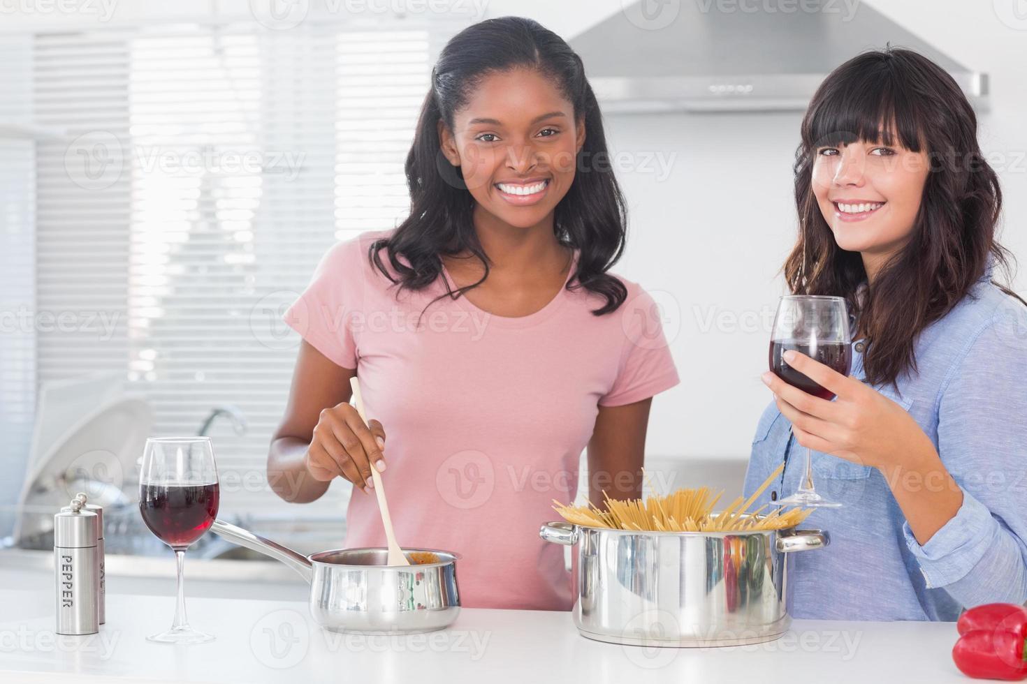 Happy friends preparing dinner together photo