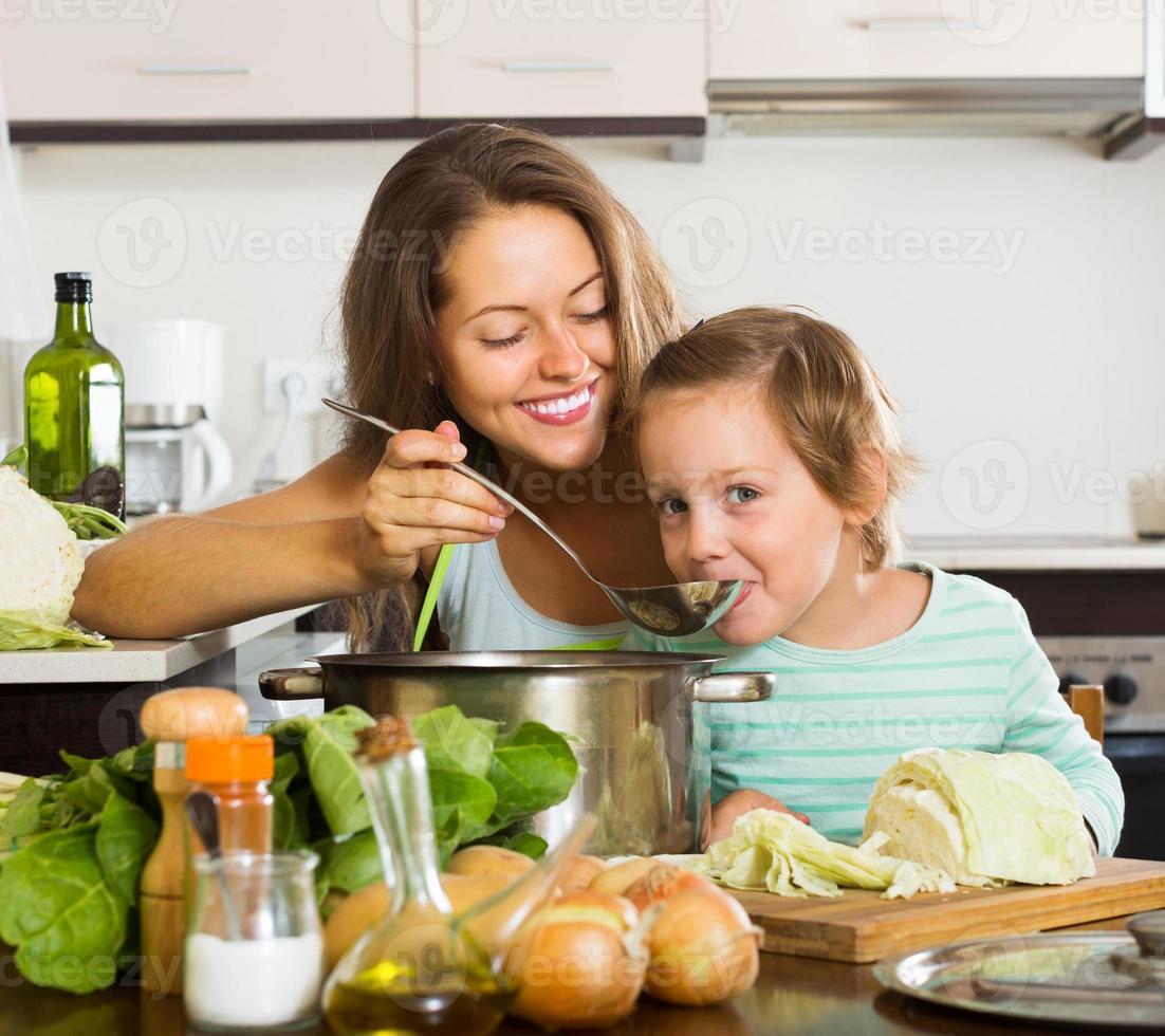 feliz madre con hija cocinando juntos foto
