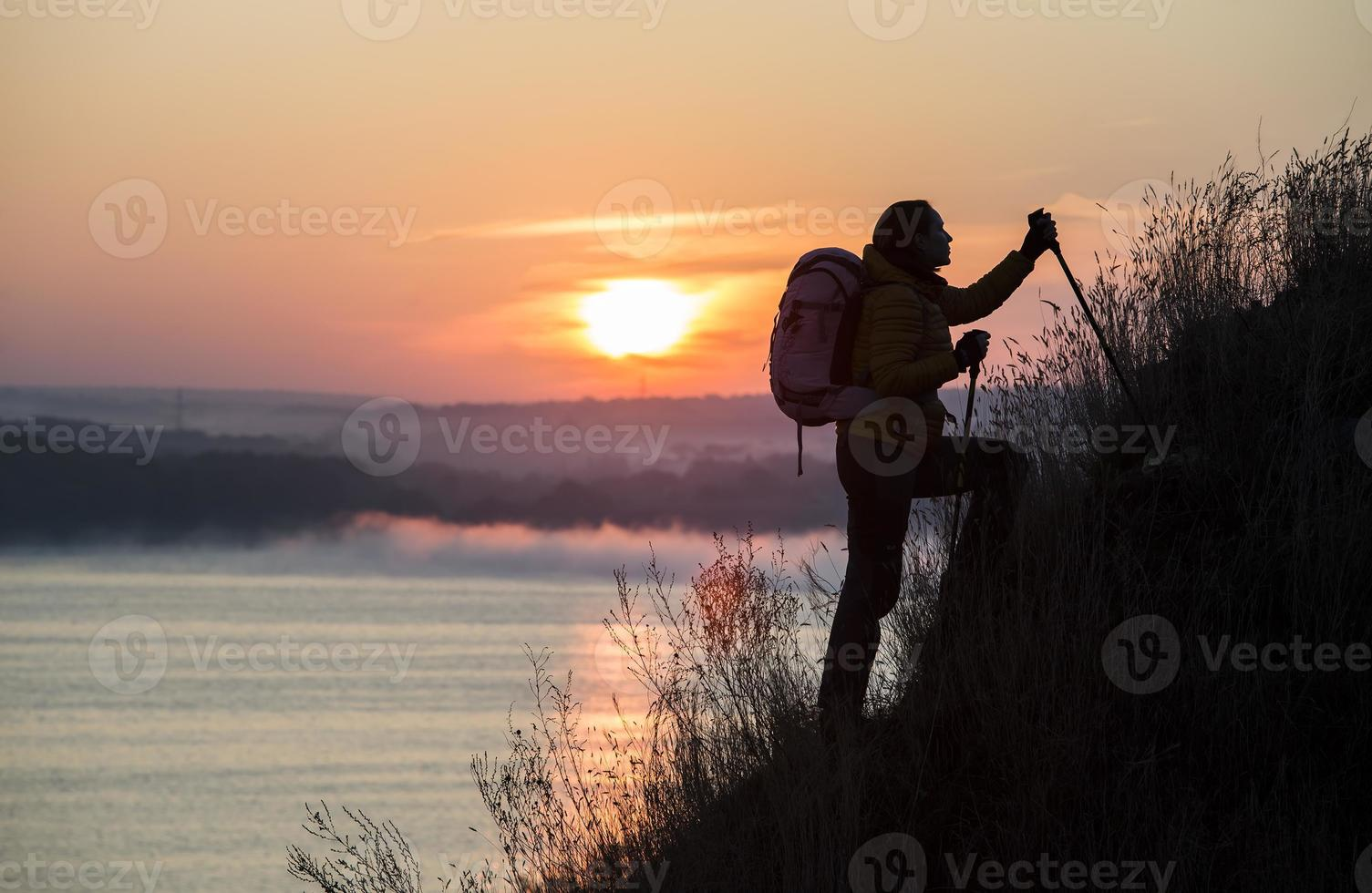 Silhouette of backpacker ascending steep hill photo