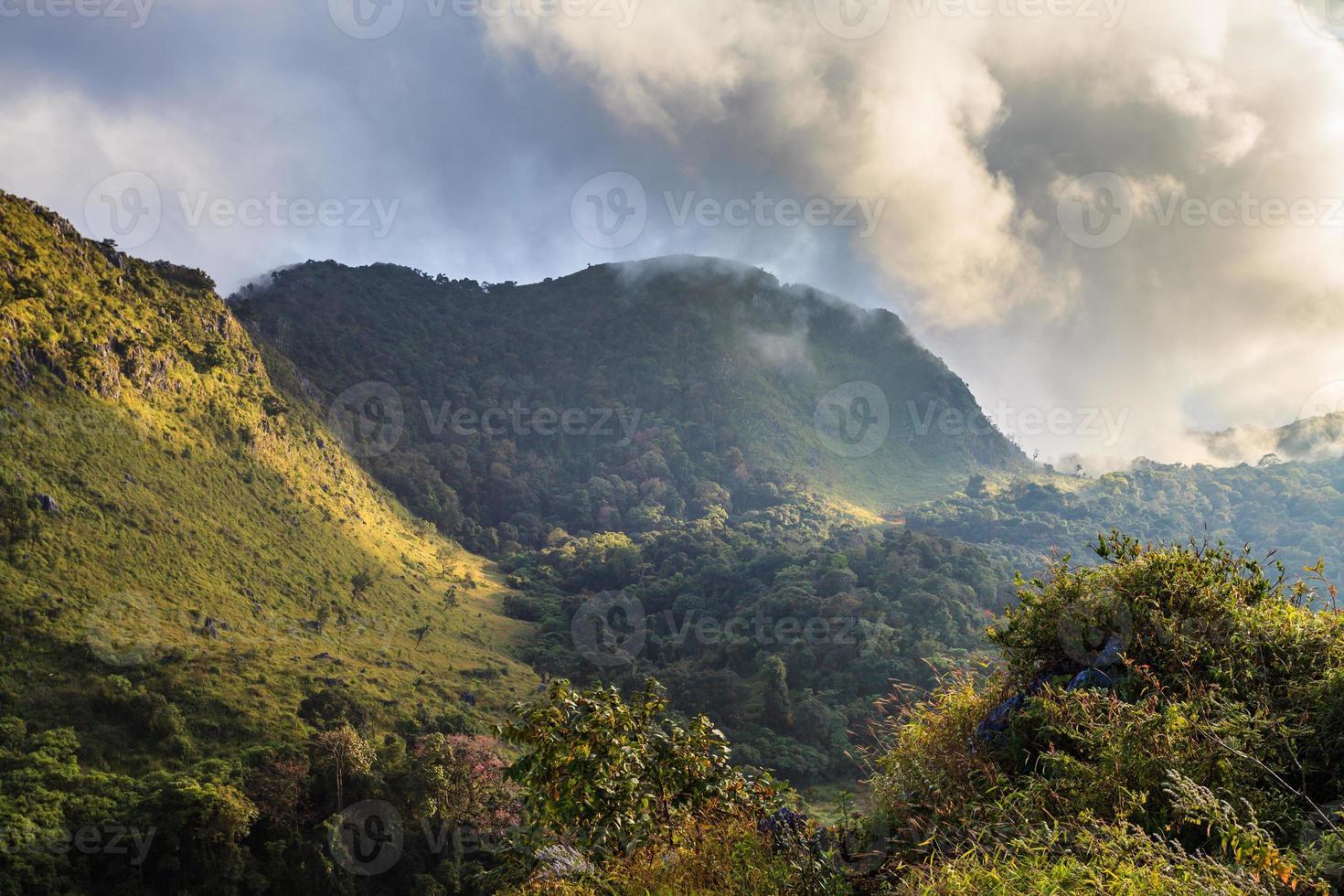 pico de la montaña y lloviendo niebla cielo azul foto