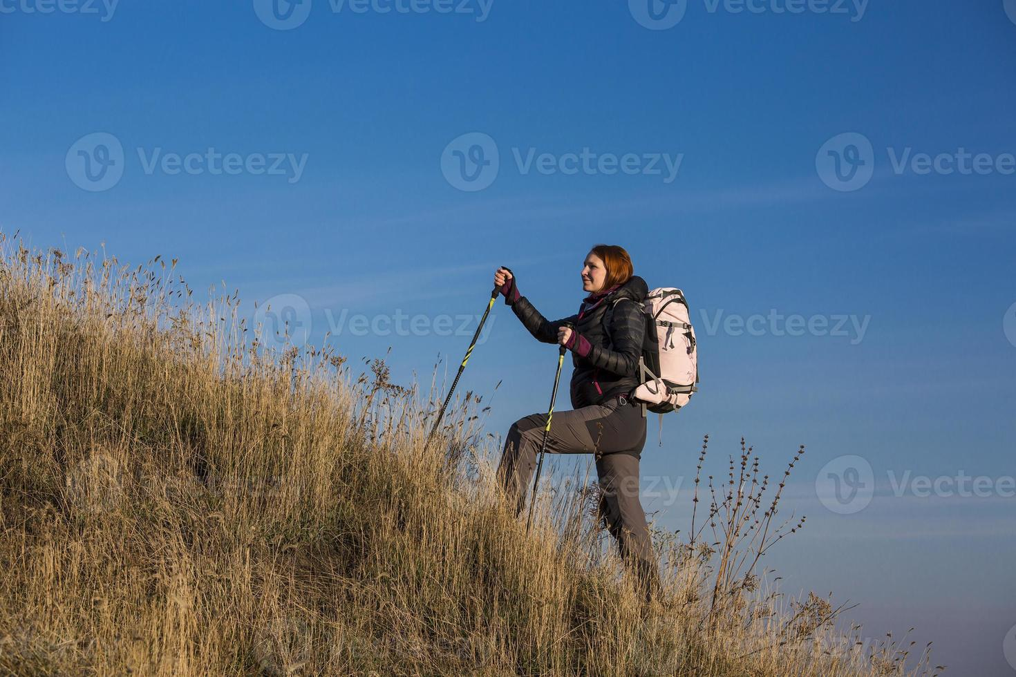 Female backpacker ascends steep hill photo