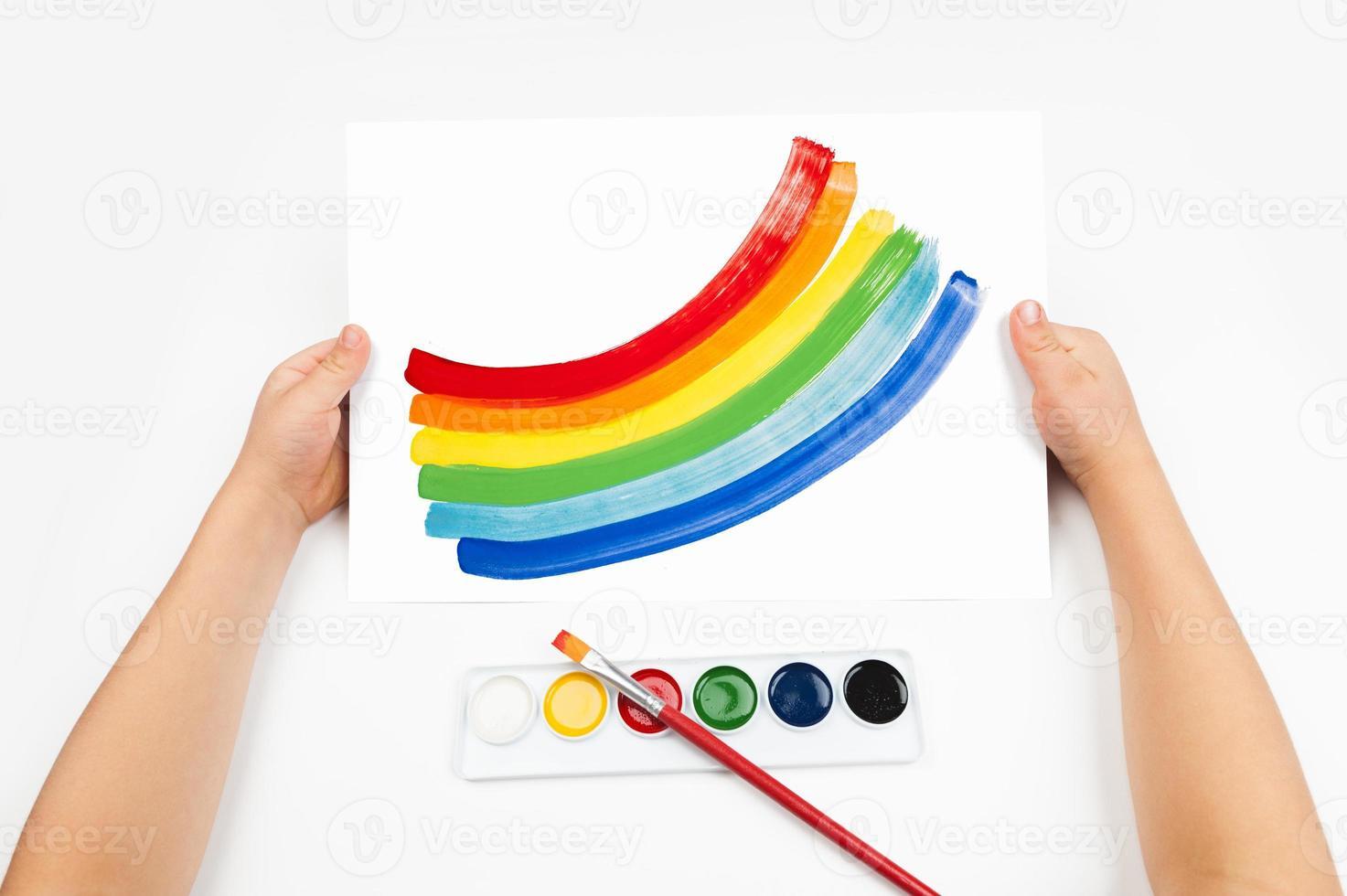 Child draws the rainbow watercolors photo