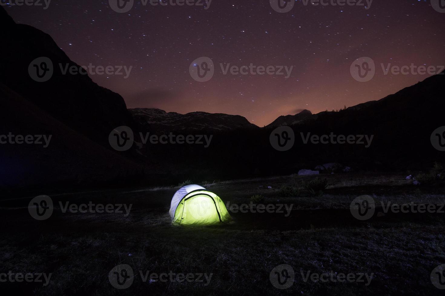 carpa de pie en una pradera de montaña bajo cielo estrellado foto