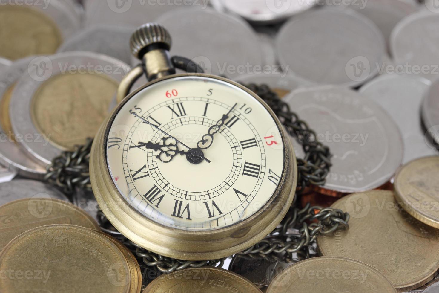 concepto financiero, antiguo reloj con monedas foto