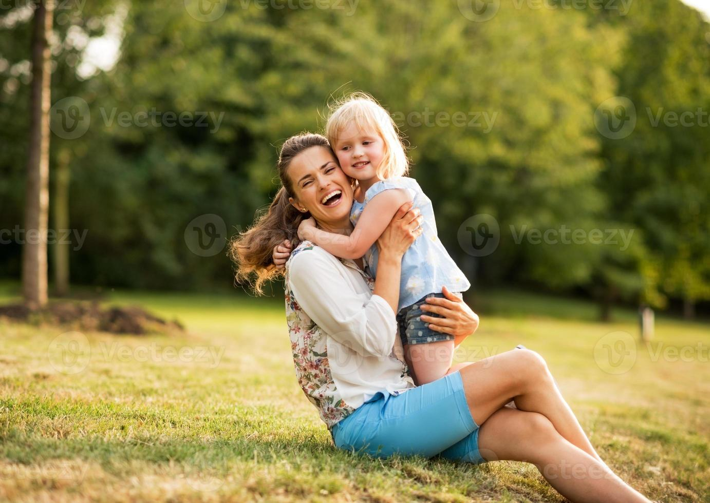 portrait of happy mother and baby girl hugging in park photo