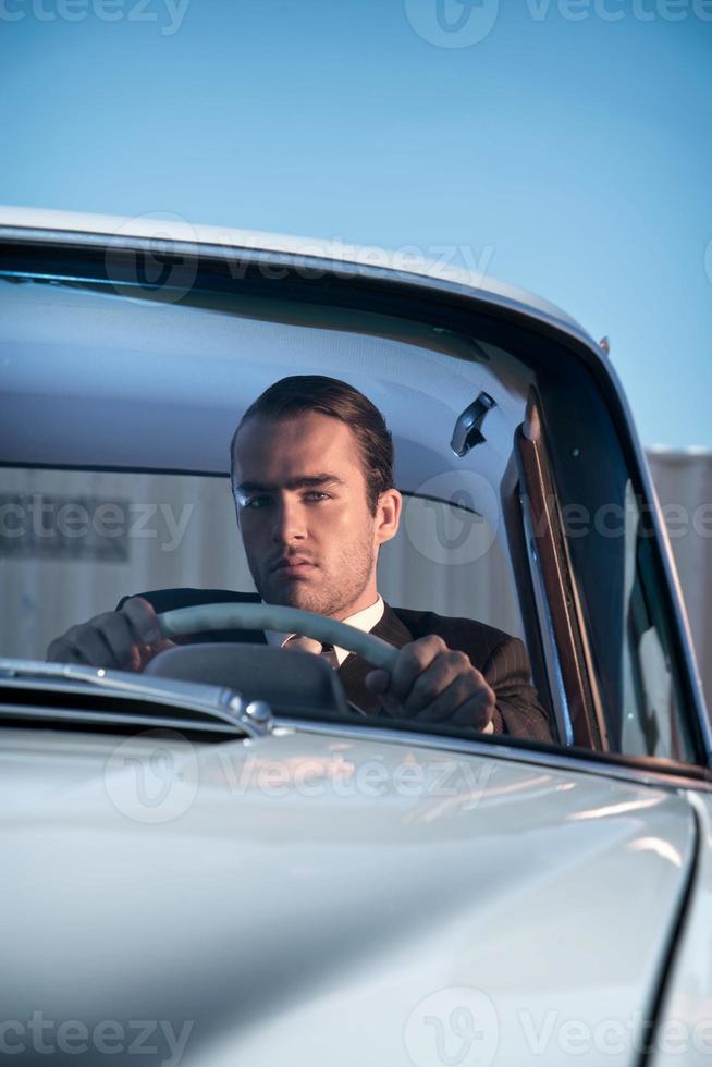 Hombre de moda retro con traje gris sentado en coche clásico. foto