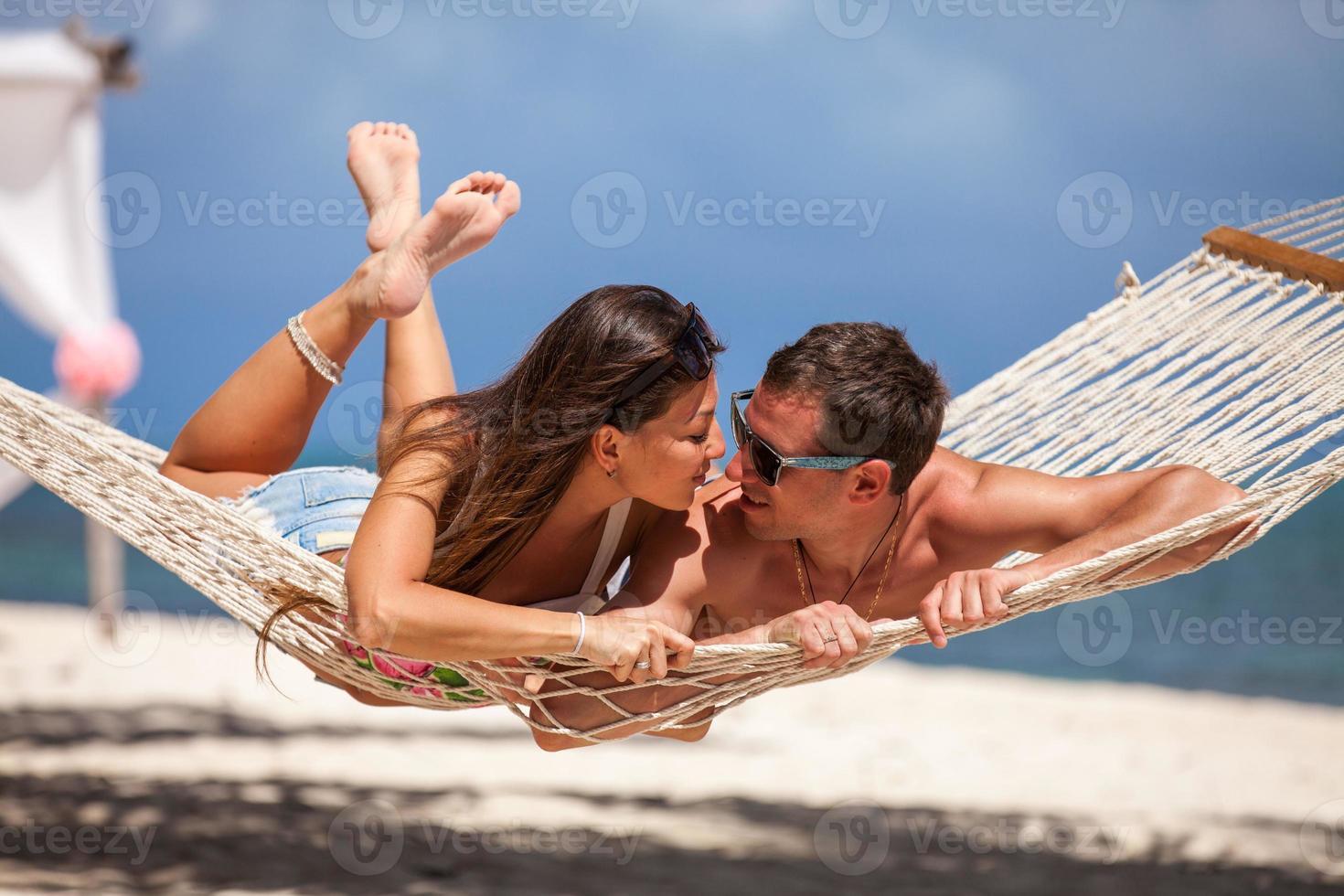 Romantic Couple Relaxing In Beach Hammock photo