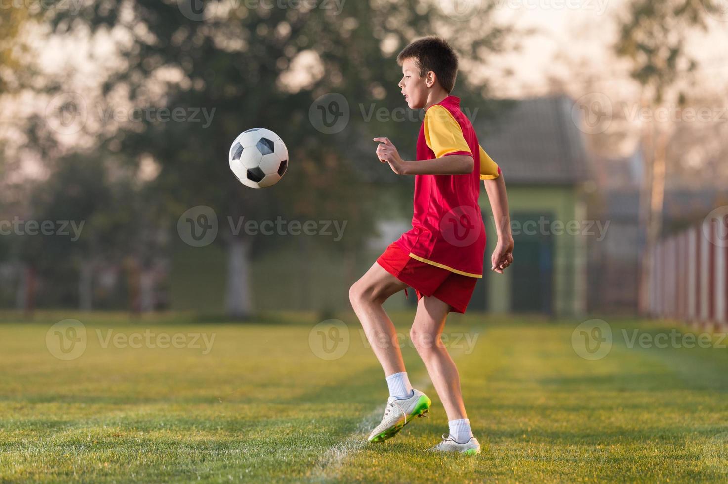 niño jugando al fútbol foto