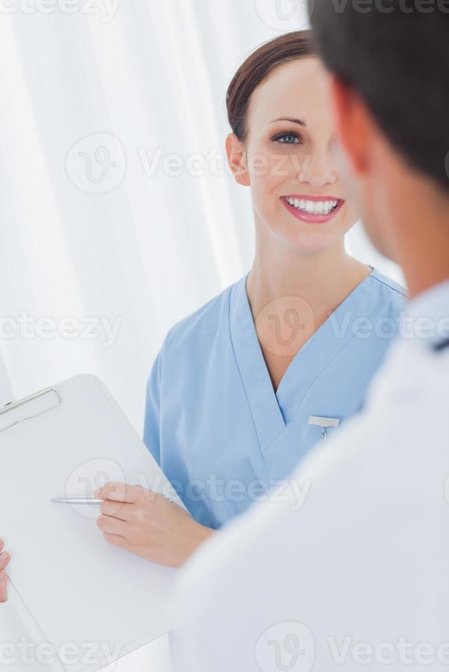 Cheerful pretty surgeon talking with a doctor photo