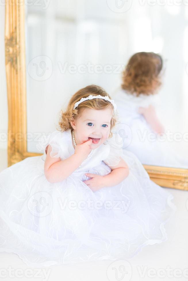 Beautiful toddler girl in white dress sitting next big mirror photo