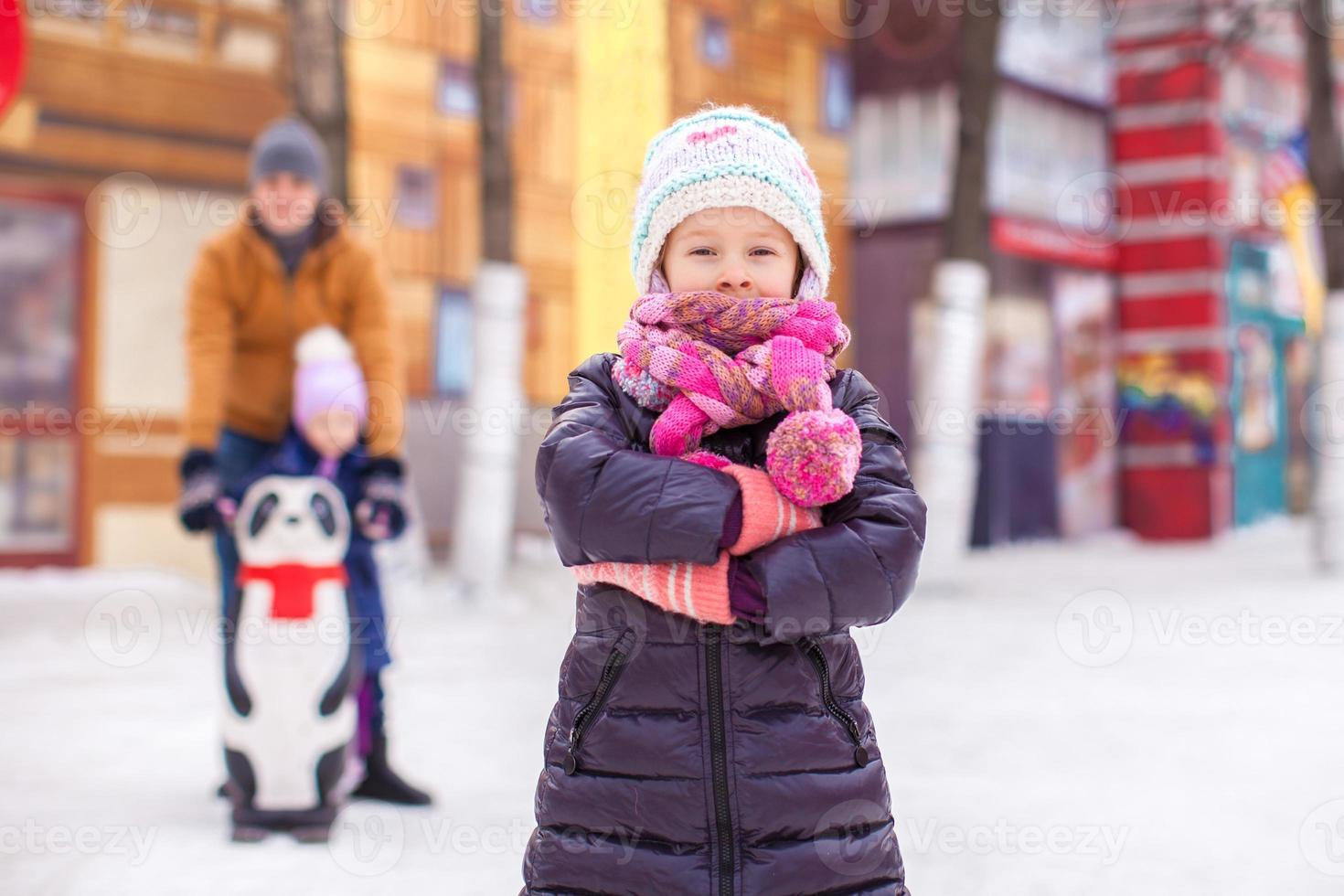 Charming girl on skating rink, dad with little sister background photo