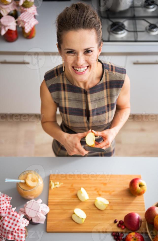 Retrato de feliz joven ama de casa cortando manzana para mermelada foto