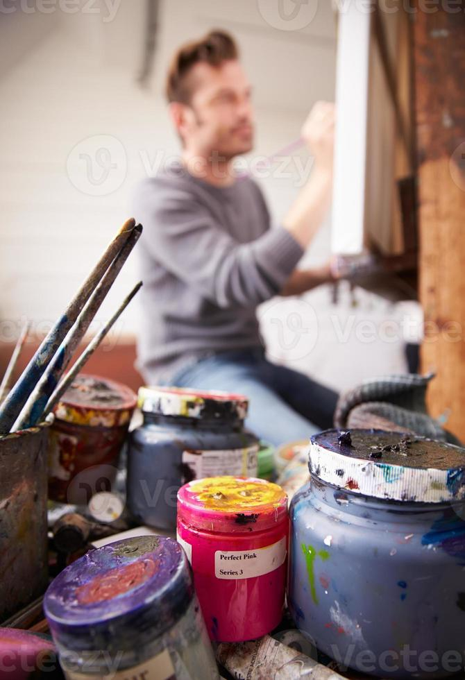 Male Artist Working On Painting In Studio photo
