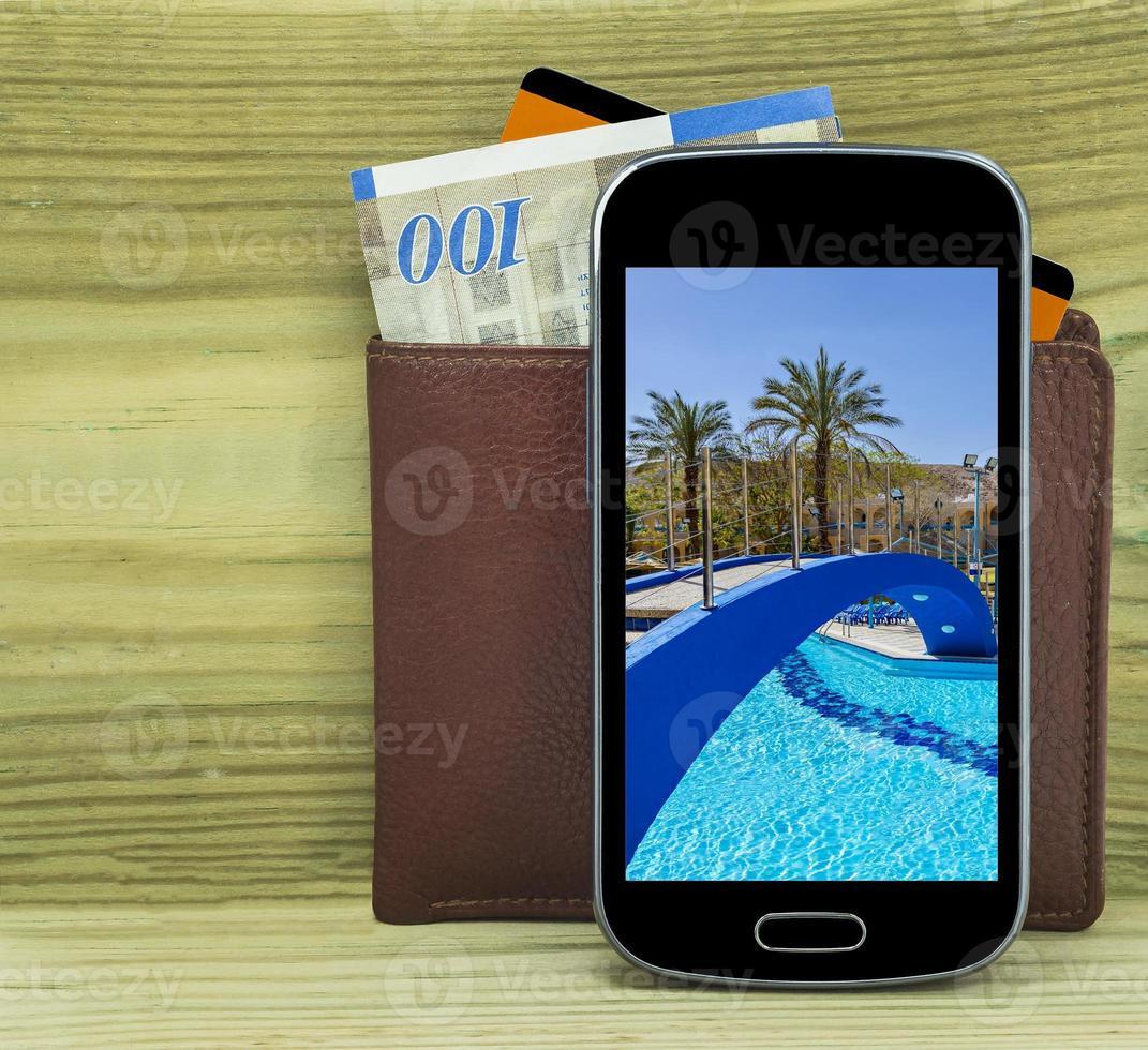 teléfono inteligente con billetera, dinero y tarjeta de crédito foto