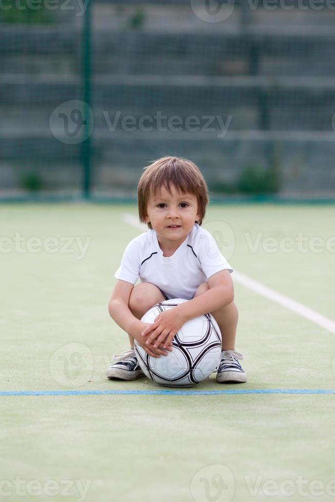 niño lindo, jugando al fútbol foto