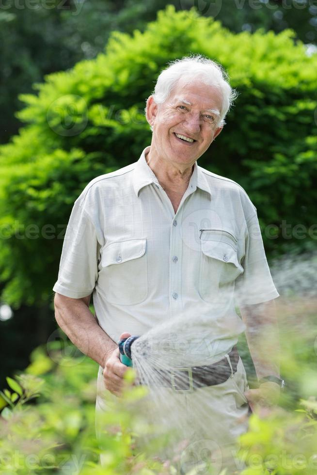 Elder gardener with hosepipe photo