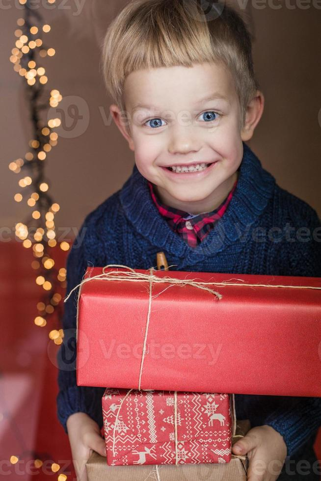 Portrait of adorable kid with gift boxes. Christmas. Birthday photo