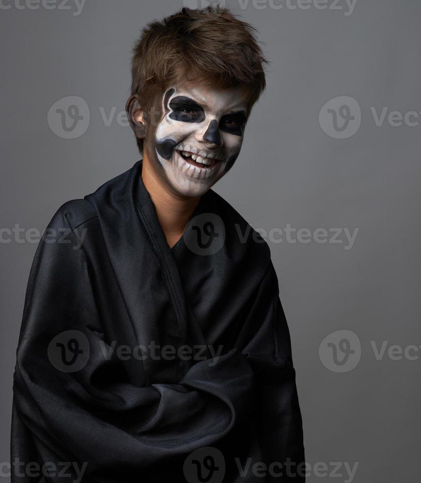 adolescente con maquillaje de calavera en manto negro se ríe foto