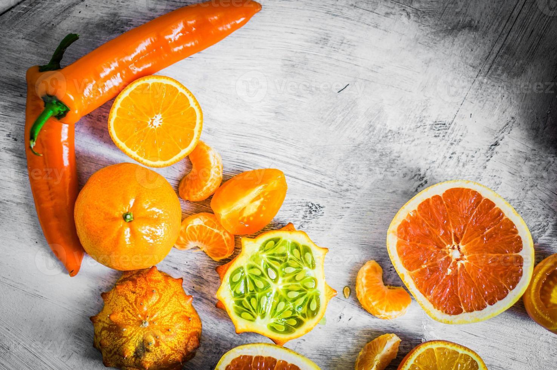 Naranja frutas y verduras sobre fondo rústico foto