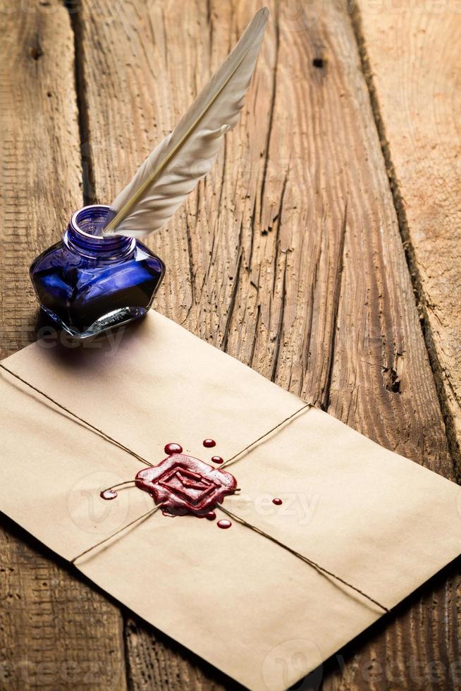 tintero de tinta azul con pluma en el sobre y sellador rojo foto