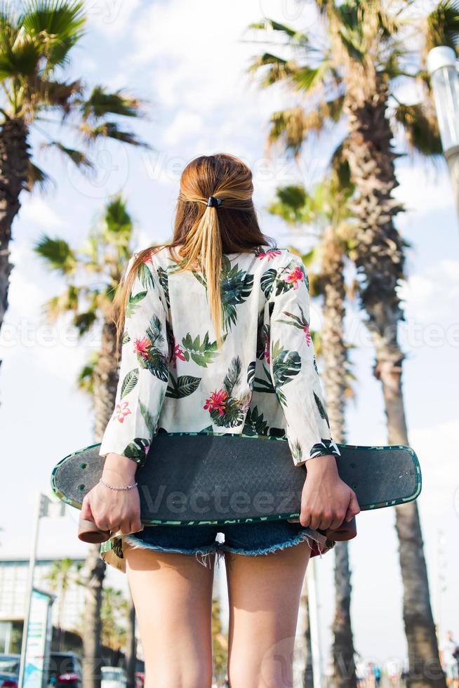 Elegante mujer con penny board de pie contra el cielo tropical foto