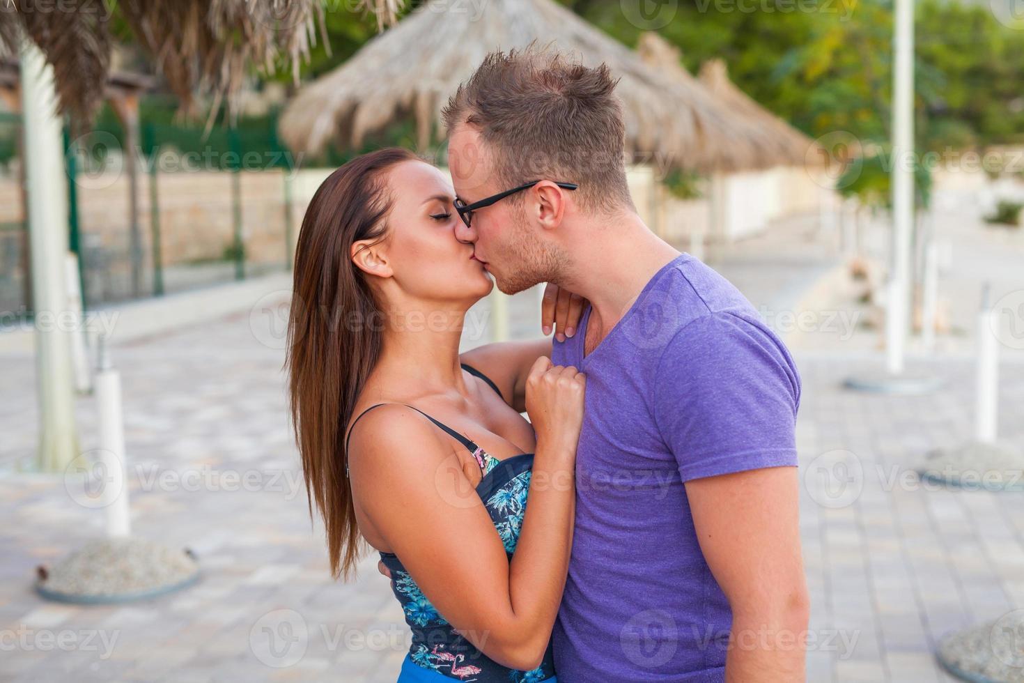 Pareja de pie en la playa y besos. son felices. foto