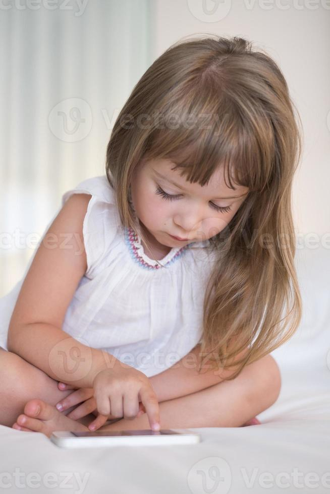 Cute Little girl using mobile phone at home photo